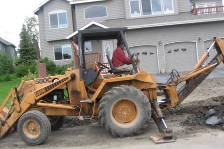 backhoe evening out a residential front yard