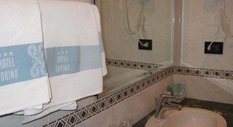 bagno con lavabo, specchio e asciugamani
