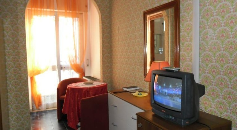 vista laterale di una stanza di albergo con parete decorata, tenda trasparnte e arredamento