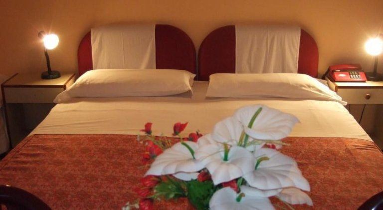 vista frontale di una camera da letto con un vaso di fiori e arredamenti