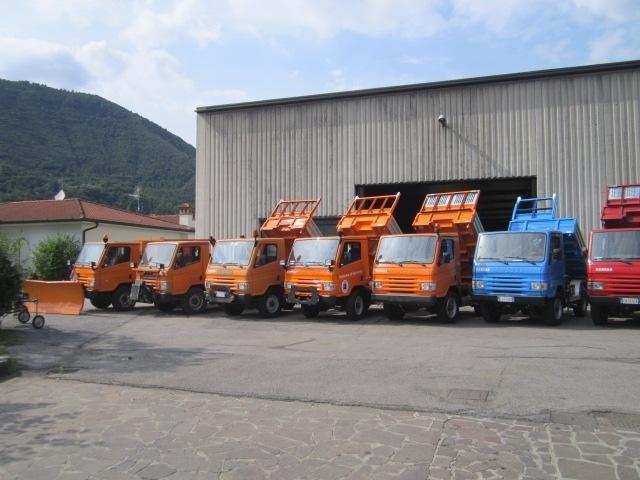 dei camion di diversi colori con dei rimorchi ribaltabili
