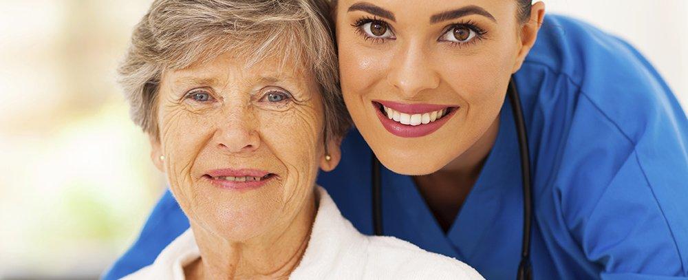 personale di servizio e una donna anziana sorridono in posa per una foto
