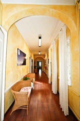 corridoio con porte ai lati e divanetti di paglia