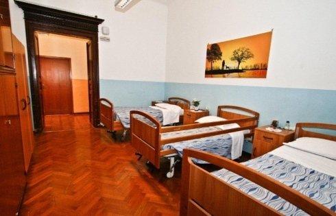 vista laterale di una stanza con tre letti singoli e spalliera