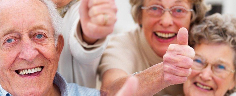 persone anziane in posa per una foto con il pollice alzato