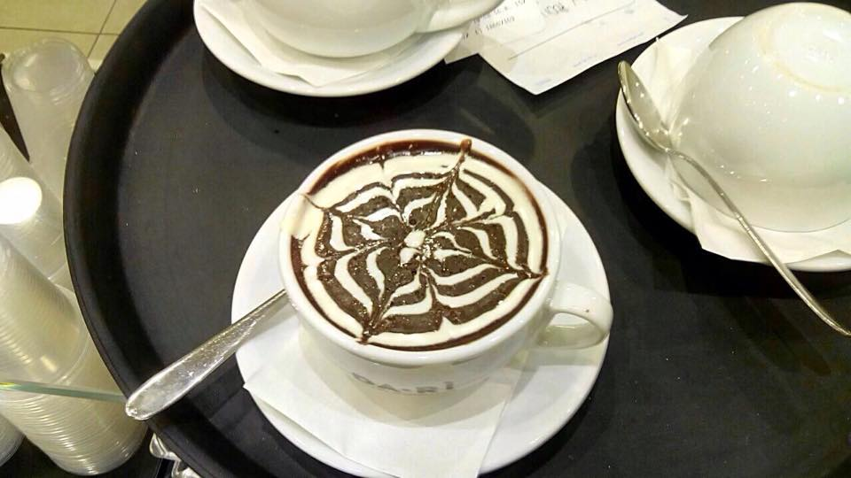una tazza di cappuccino con sopra dello sciroppo al cioccolato