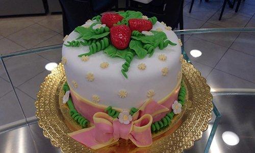 una torta con glassa e decorata con un fiocco rosa