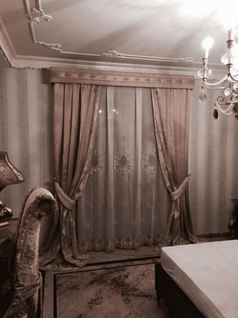 una tenda bianca e beige all'interno di una stanza con arredi d'epoca