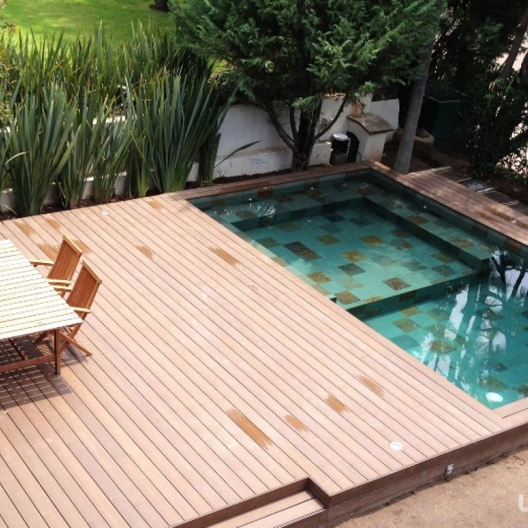 una passerella di legno con piscina a destra e tavolo con due sedie a sinistra
