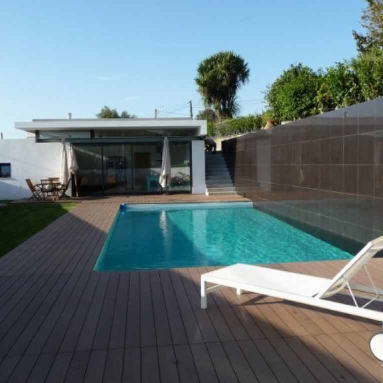 una passerella di legno con piscina e una sdraio bianca