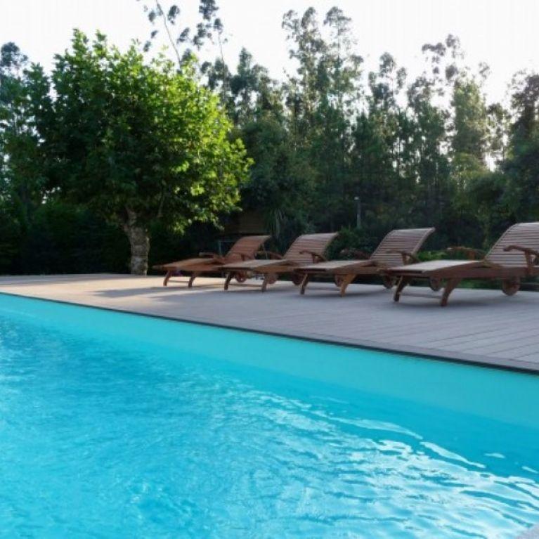 una piscina con diverse sdraio vicino
