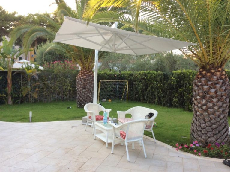 ombrellone bianco sopra arredi da giardino bianchi