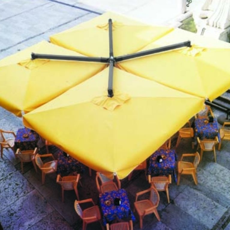 ombrellone giallo sopra numerose sedie di legno