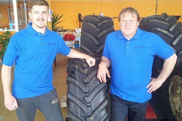 due persone vicino a un pneumatico di un trattore