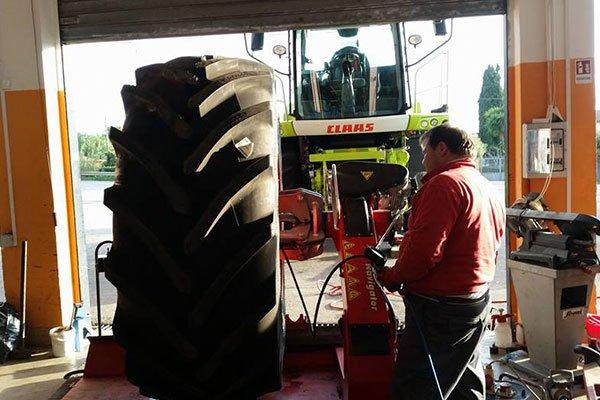 un uomo in un'officina e accanto un pneumatico di un trattore