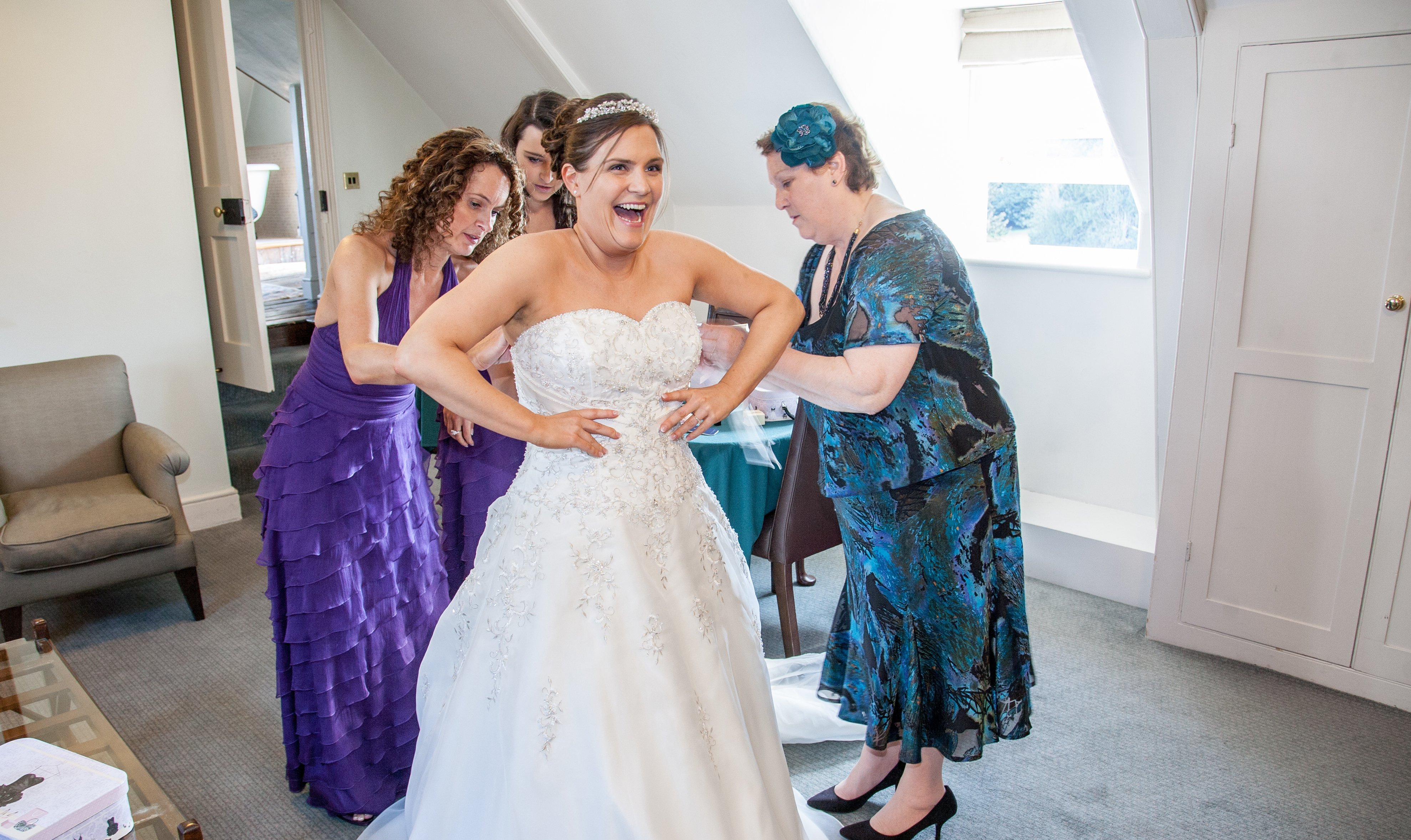 Laughing bride having her dress adjusted by her Mum and bridesmaids