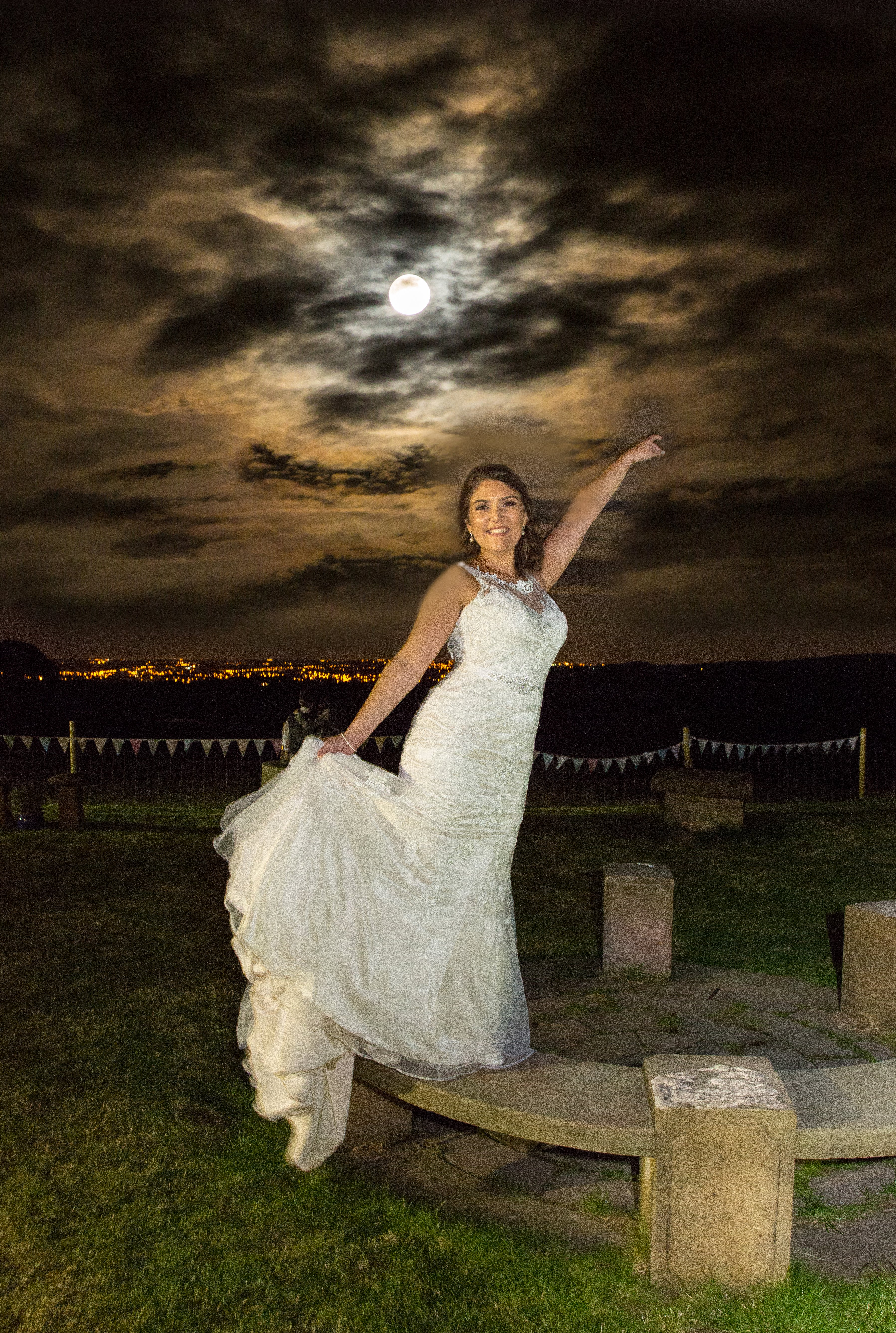 A bride posing at dusk, with lights and darkening sky behind her