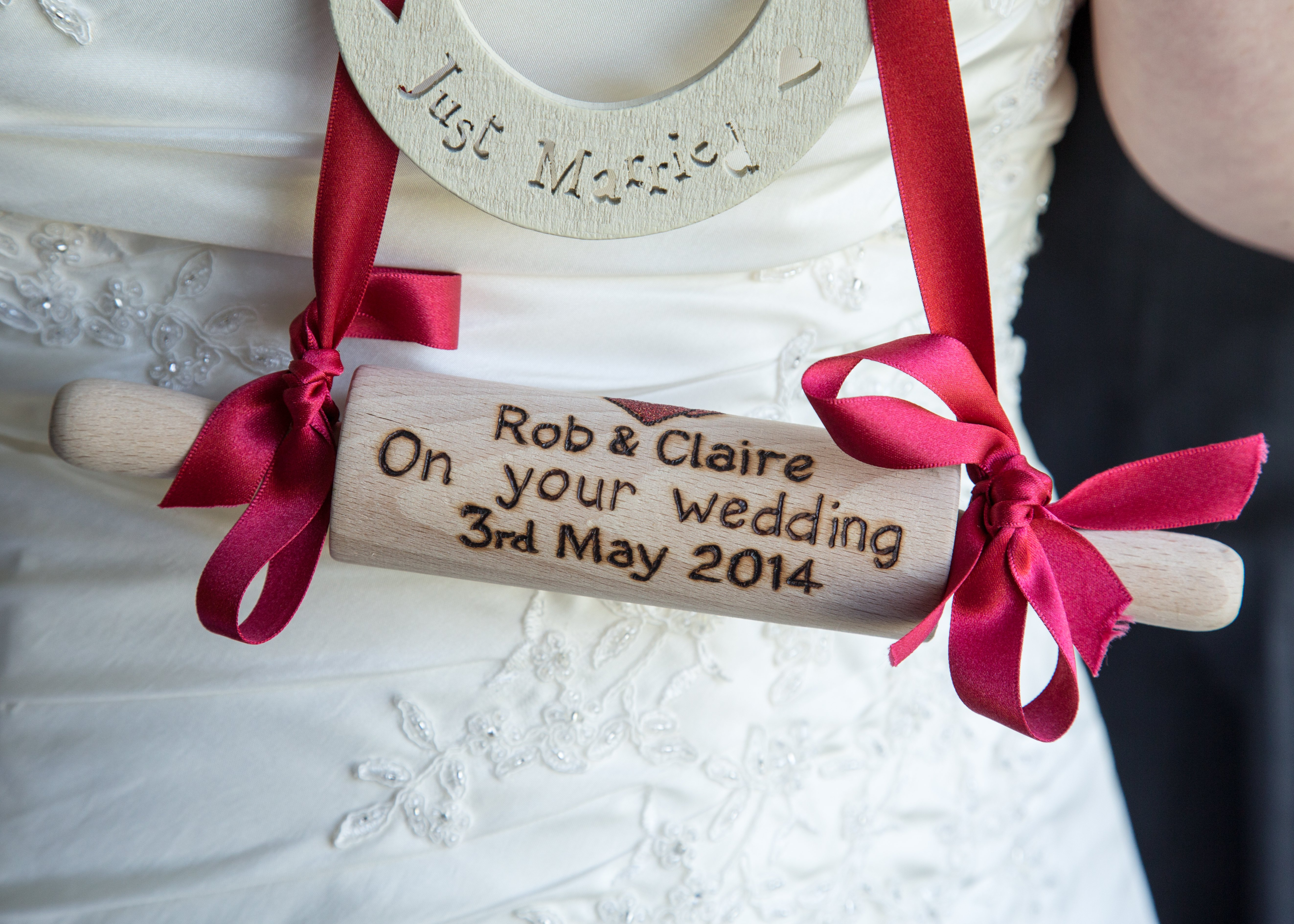 A white horseshoe and scroll on a red ribbon, for the 2004 wedding of Rob and Claire