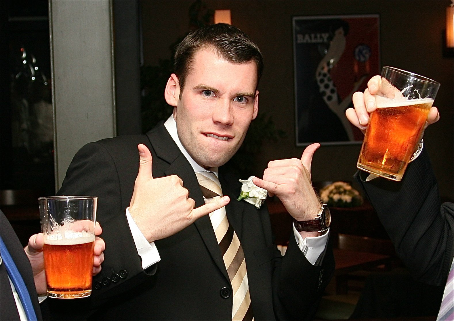 Man in black suit and stripe tie, flanked by hands holding pints of beer