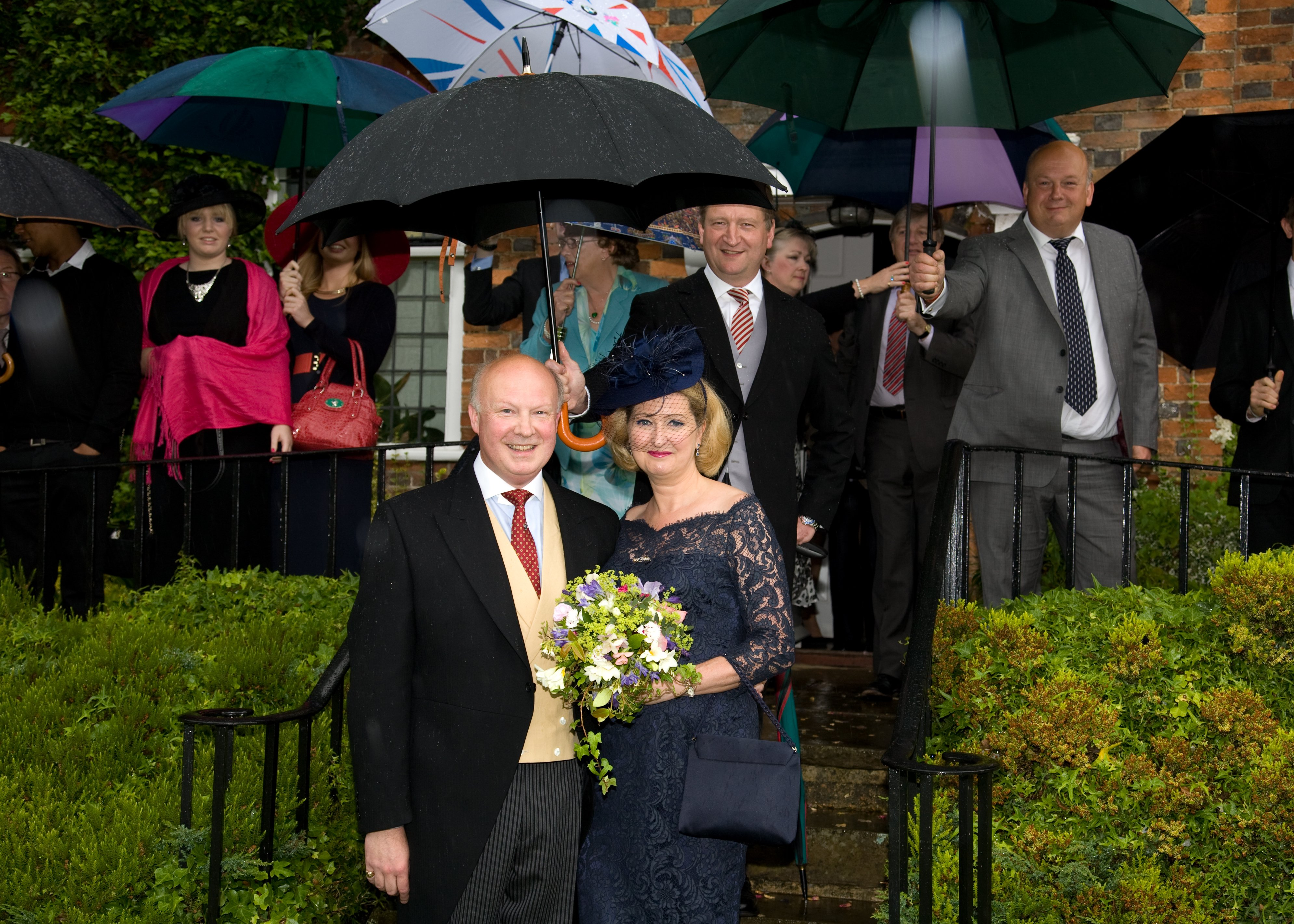Guests holding umbrellas over themselves and a bride and groom