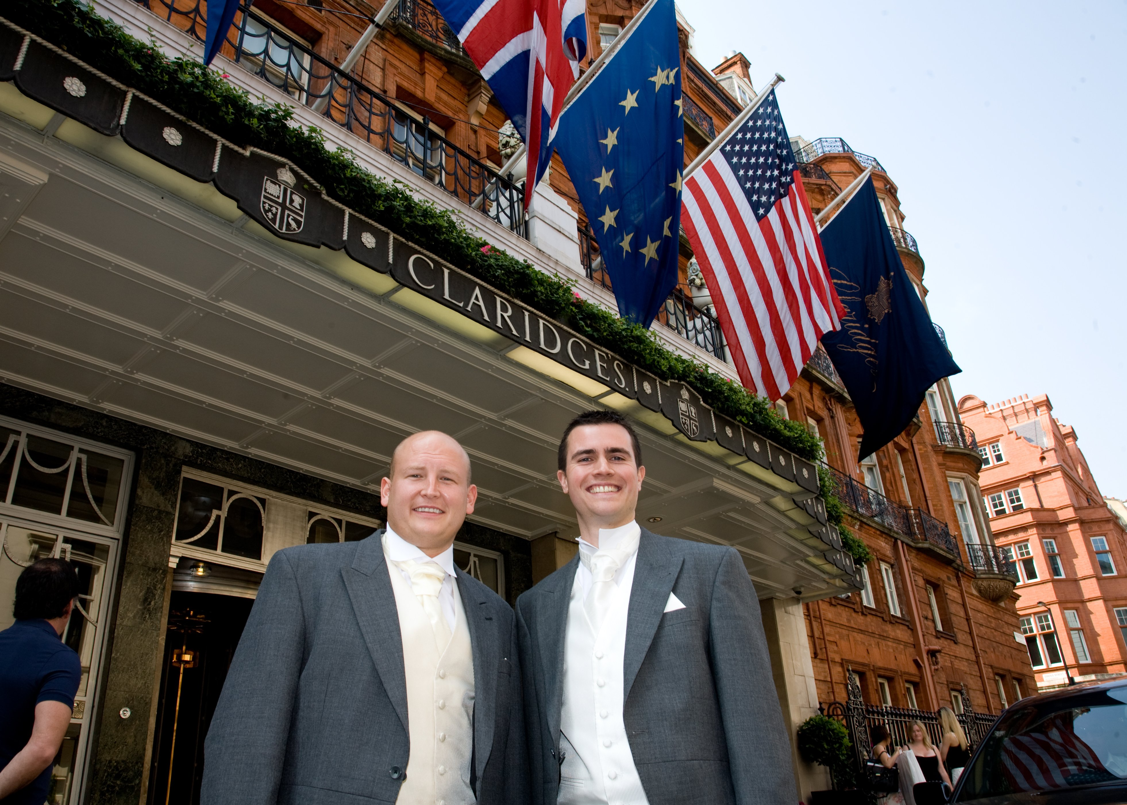 Two men in white tie dress, standing in front of Claridge's