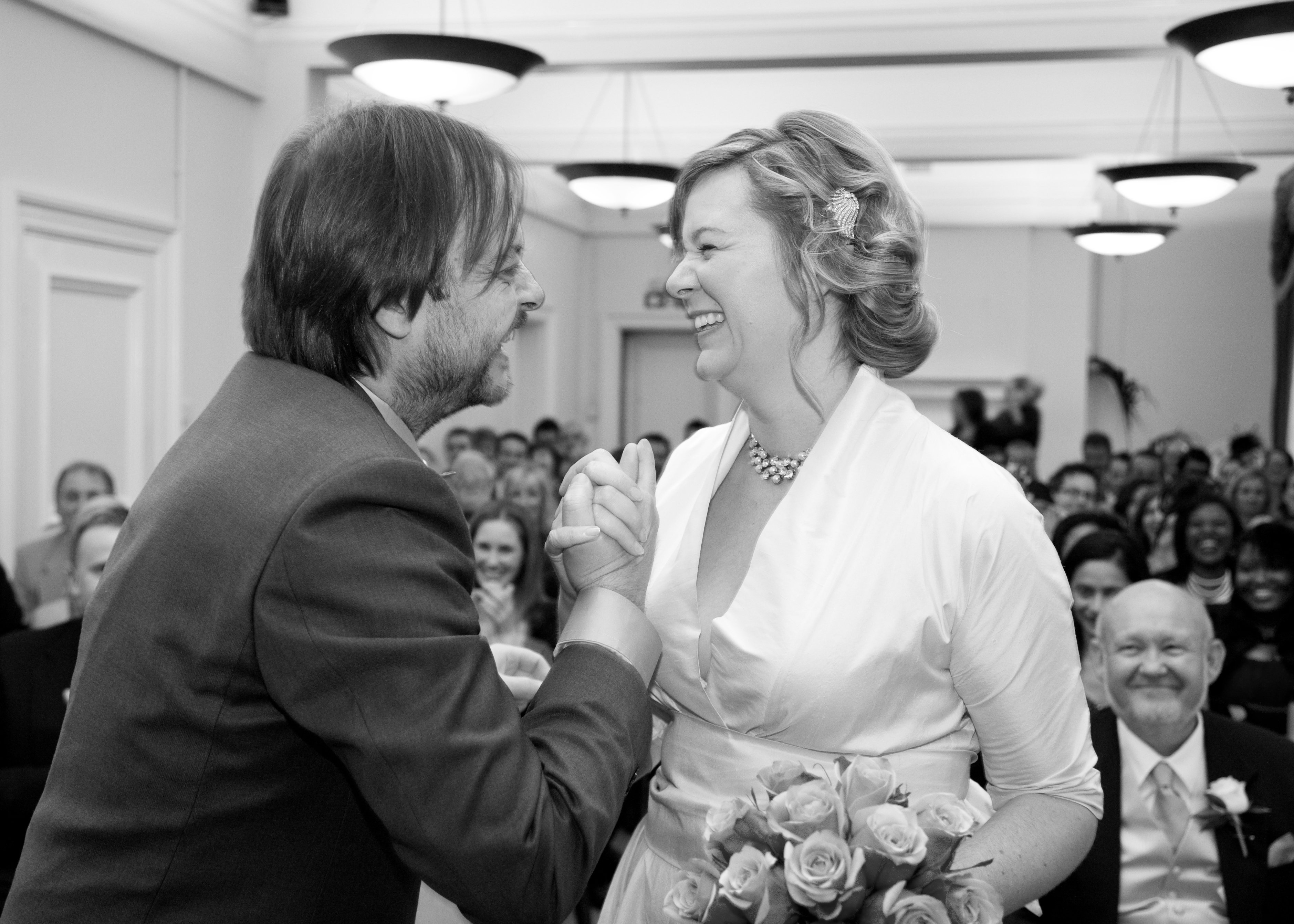 Bride and groom smiling at each other during a registry office wedding