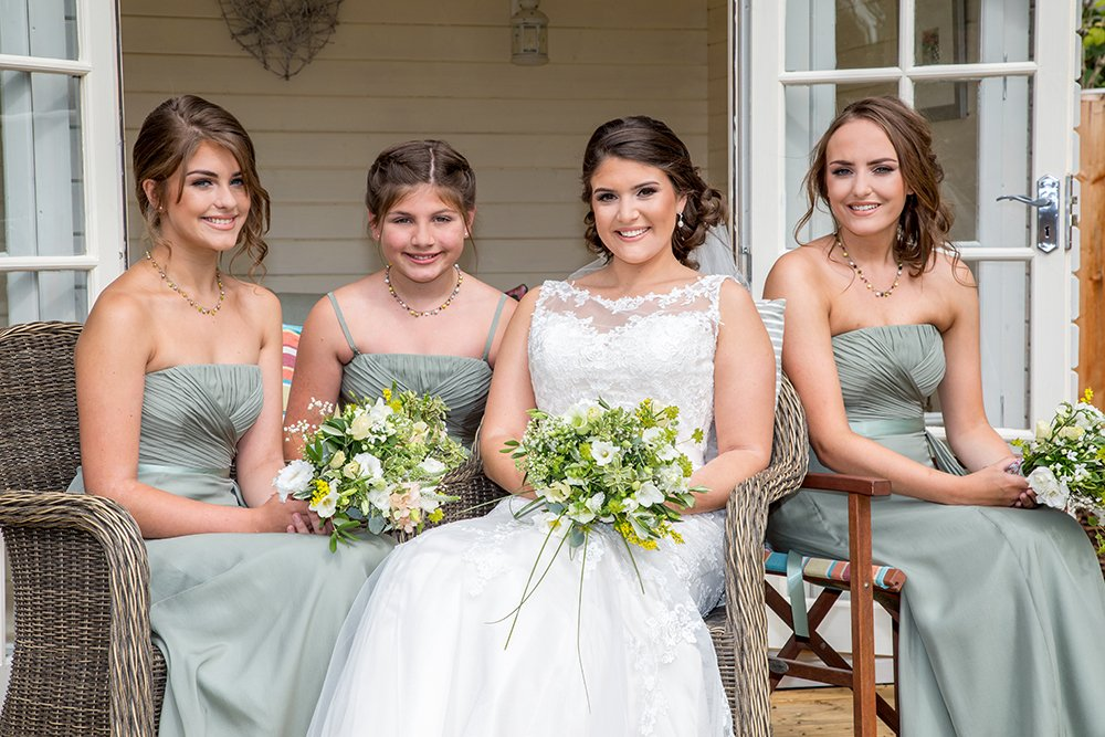 Bride in white with three bridesmaids in dove-grey