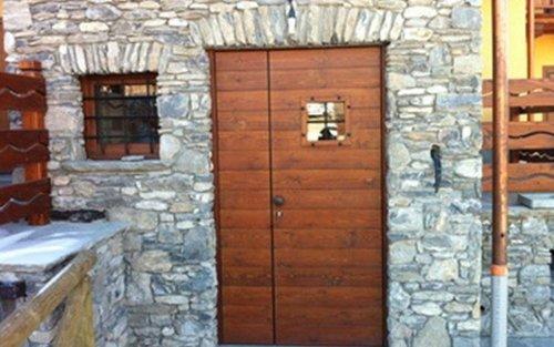 portone in legno e parete in pietra