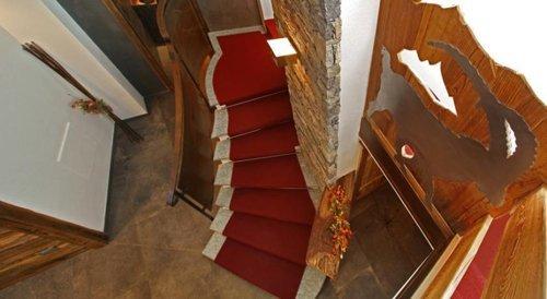 vista angolare delle scale interne con tappeto rosso