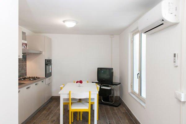 una cucina con sulla sinistra i fornelli e in fondo un forno in acciaio, in centro un tavolo bianco con sedie gialle e sulla destra un mobile tv nero con sopra una televisione