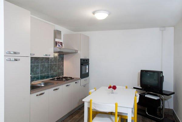 la cucina vista da vicino con i fornelli sulla sinistra, il tavolo bianco con le sedie gialle in centro e sulla destra una tv su un mobiletto