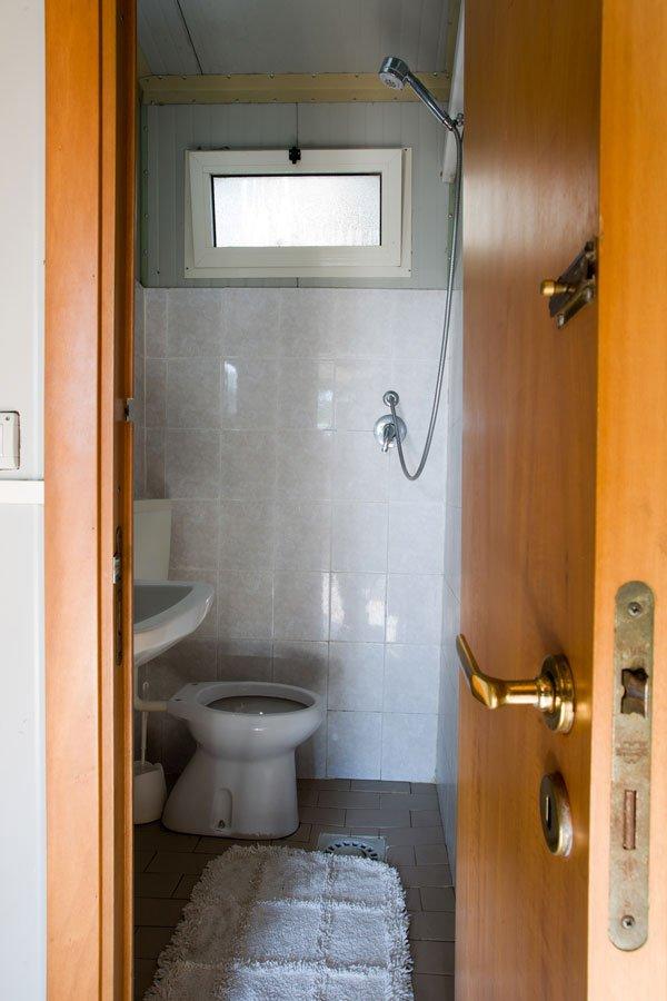 un bagno con un wc sulla sinistra una doccia a muro e scarico a vista sul pavimento con accanto un tappetino bianco