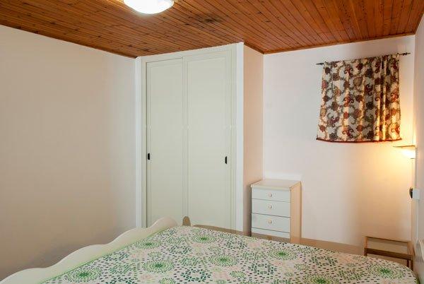camera da letto con soffitto in legno, un armadio bianco, una cassettiera e un letto con un coprimaterasso bianco a disegni verdi