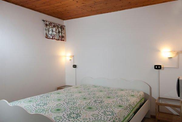 la camera da letto vista da un'angolazione diversa con vista del letto con il coprimaterasso di color bianco a disegni verdi r accanto due comodini in vetro e legno e delle luci a muro accese