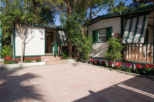 vista dall'esterno di due casette bianche e verdi con degli alberi e delle aiuole con dei fiori rossi
