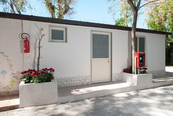 vista dall'esterno di un piccolo edificio bianco con una porta, una finestrella, un estintore a muro e dei vasi rialzati con dentro dei fiori rossi