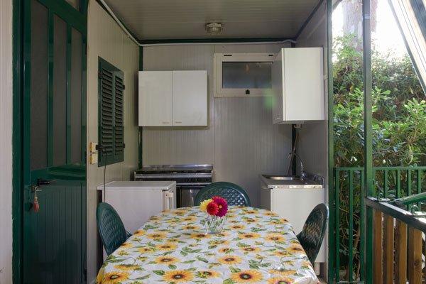 all'esterno della casetta un tavolo con una tovaglia bianca a girasoli gialli con un vaso di vetro con dei fiori rossi e gialli e dietro un lavandino, un frigorifero e dei fornelli