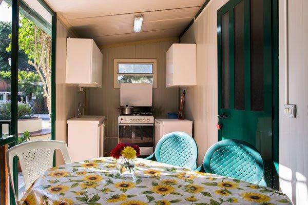 esterno della casetta con un tavolo con tovaglia bianca a girasoli gialli, sedie verdi e davanti un lavandino, dei fornelli e un frigorifero