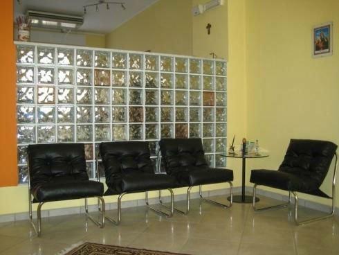 una sala d'attesa con quattro sedie di pelle