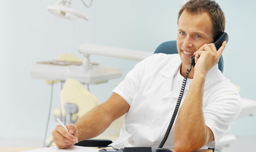 Dentist talking on phone about dental health practices in Honolulu, HI