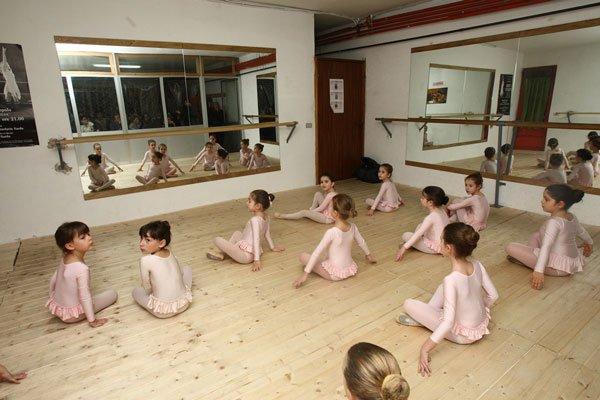delle bambine ballerine sedute in una sala attorniata da specchi e una sbarra in legno per degli esercizi di danza