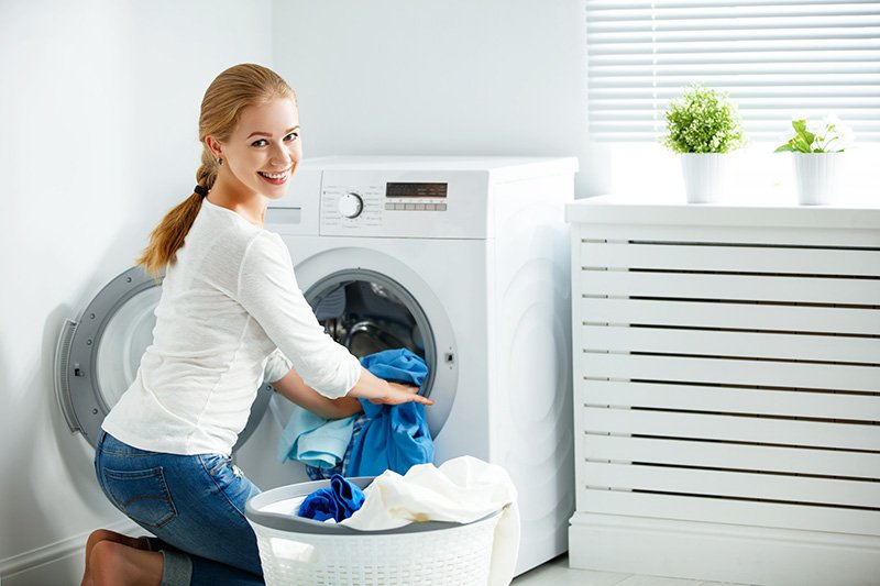 Woman in the laundry room near the washing