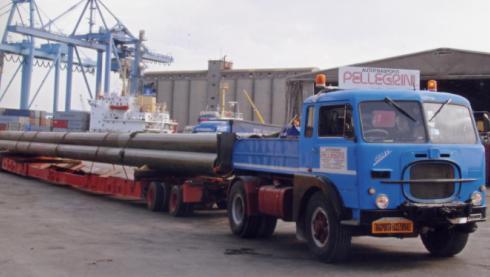 un camion blu con dei lunghi tubi di ferro sul rimorchio