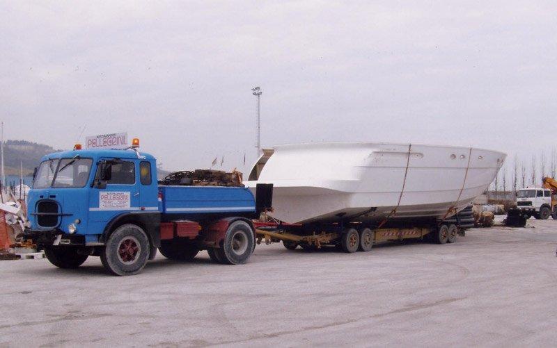 un camion blu con un rimorchio con sopra uno scafo bianco