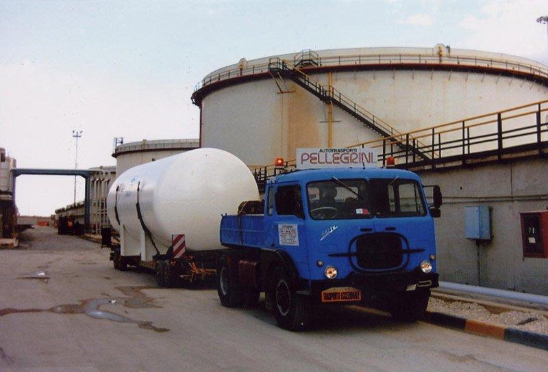 un camion blu con un rimorchio che trasporta una grande tanica