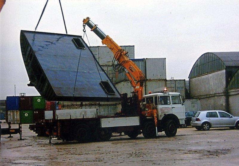 un camion bianco con un braccio meccanico sul rimorchio mentre solleva un carico