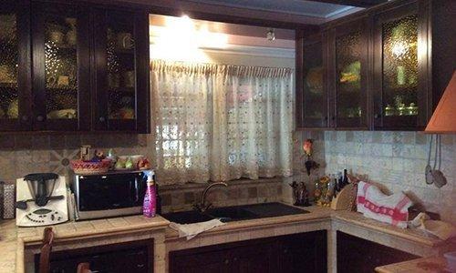 una cucina e una finestra con delle tendine bianche