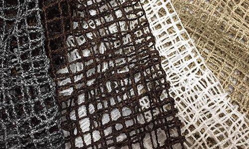 delle stoffe a rete di color grigio, marrone scuro, bianco e dorato