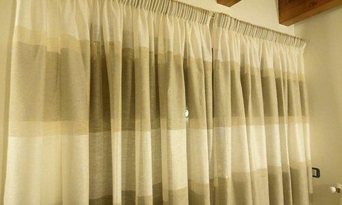 delle tende a righe di color grigio e avorio
