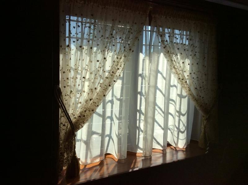 una finestra con le tende di color bianco e color avorio con disegni di stelline